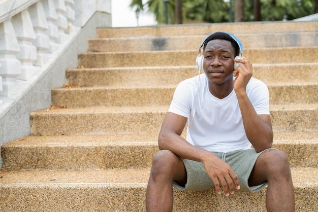 Молодой красивый африканский мужчина сидит на лестнице во время прослушивания музыки в наушниках