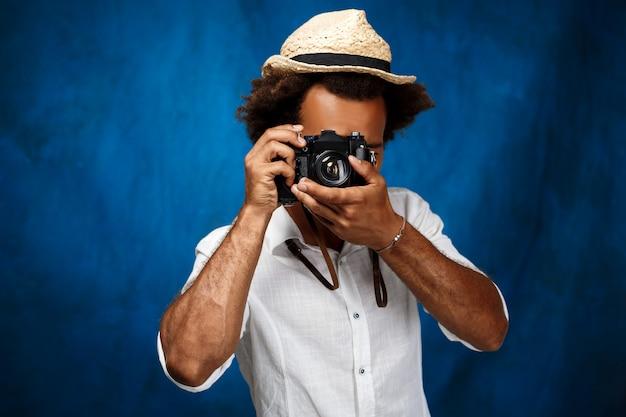 Giovane uomo africano bello che prende foto sopra la parete blu.
