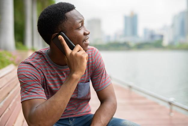 Молодой красивый африканский мужчина разговаривает по телефону в парке