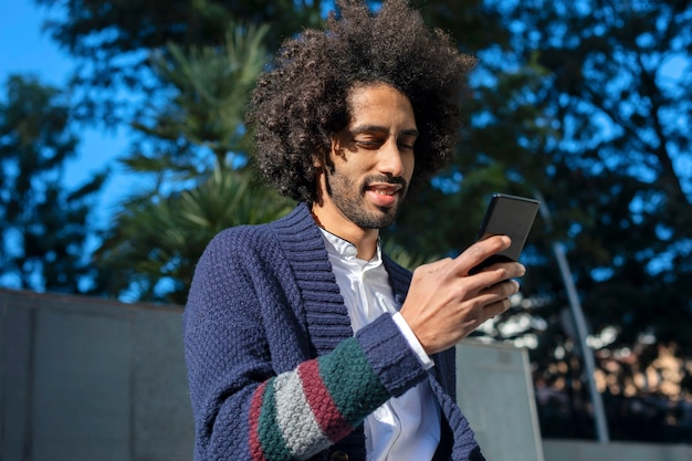 Young handsome african man using his smartphone with smile while sitting on a bench outdoors in sunny day