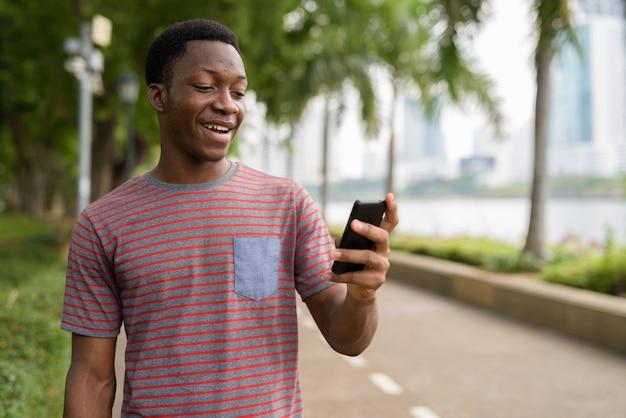 Молодой красивый африканский мужчина с помощью мобильного телефона в парке