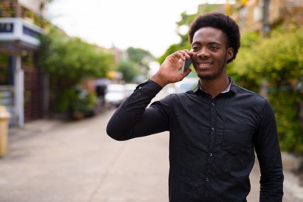 Молодой красивый африканский мужчина с помощью мобильного телефона на открытом воздухе