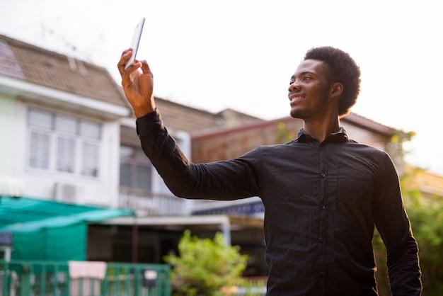 屋外で携帯電話を使用して若いハンサムなアフリカ人