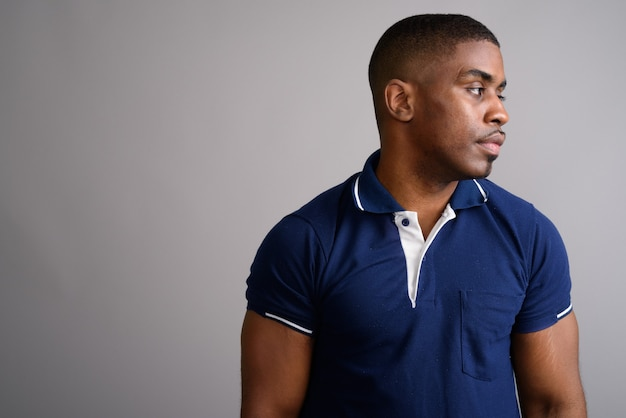 Young handsome african man wearing blue polo shirt on gray