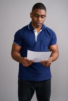 灰色の青いポロシャツを着ている若いハンサムなアフリカ人