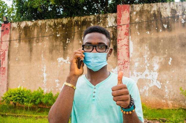 彼の携帯電話で電話をかけるフェイスマスクを身に着けている若いハンサムなアフリカ人。