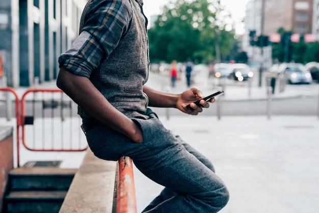 Молодой красивый афро черный человек, сидя на перила на улице в городе с помощью смартфона handheld