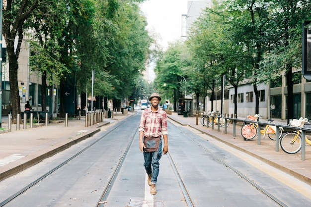 Young handsome afro black man walking in the middle on the rail outside in the city