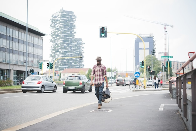 Young handsome afro black man walking in the street of the city