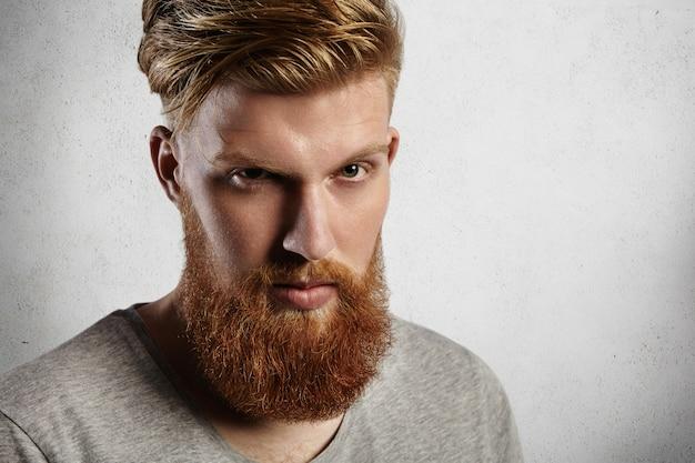 彼の金髪の眉毛の下から若いハンサムで勇敢な男。グレーのトップに丸いクルーネックのヨーロピアンヒップスター。素敵な生姜のひげと口ひげがスタイリッシュでトレンディに見えます。