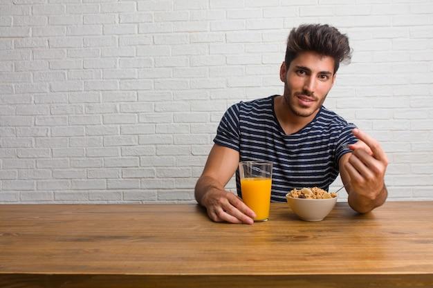 若いハンサムで自然な男が来てテーブルに座って招待