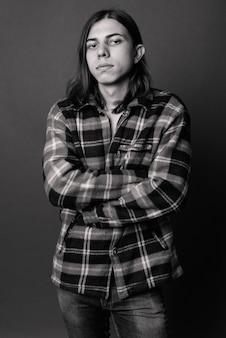 黒と白の灰色の壁に対して長い髪を持つ若いハンサムな両性具有の流行に敏感な男