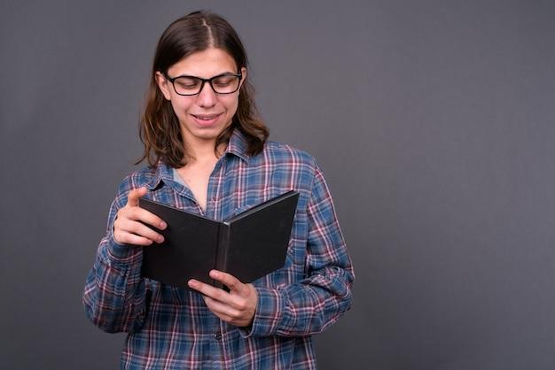 灰色の壁に長い髪を持つ若いハンサムな両性具有の流行に敏感な男