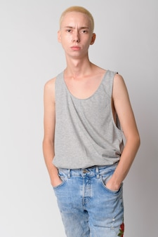 Young handsome androgynous man against white wall