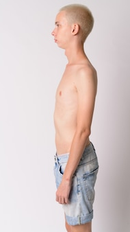 Young handsome androgynous man shirtless against white wall