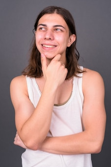 Young handsome androgynous man with long hair against gray wall