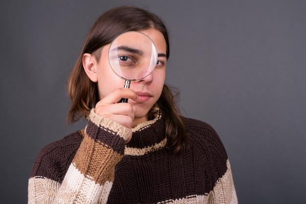 회색 벽에 겨울을위한 준비가 긴 머리를 가진 젊은 잘 생긴 남녀 양성 남자