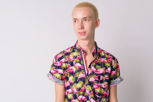 Young handsome androgynous tourist man in bohemian shirt against white wall