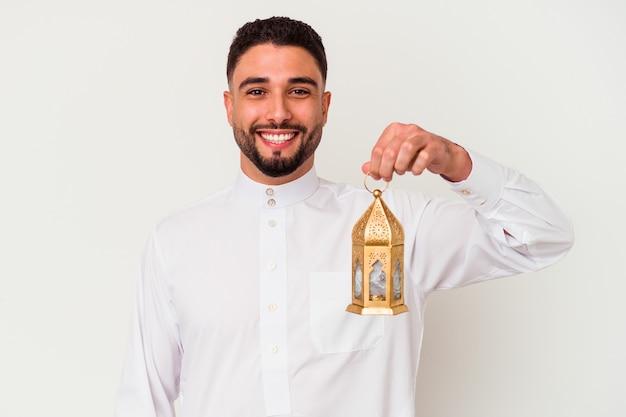 Молодой красивый арабский мужчина держит лампу