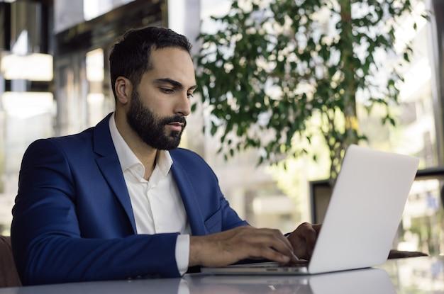 Молодой красивый арабский бизнесмен, работающий в современном офисе