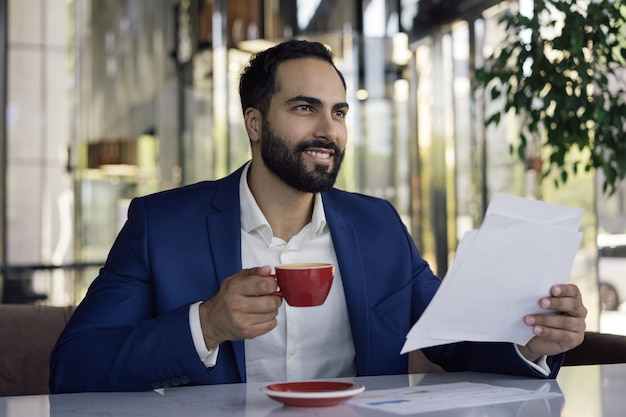 Молодой красивый арабский менеджер, работающий с документами, сидя на рабочем месте, держа чашку кофе