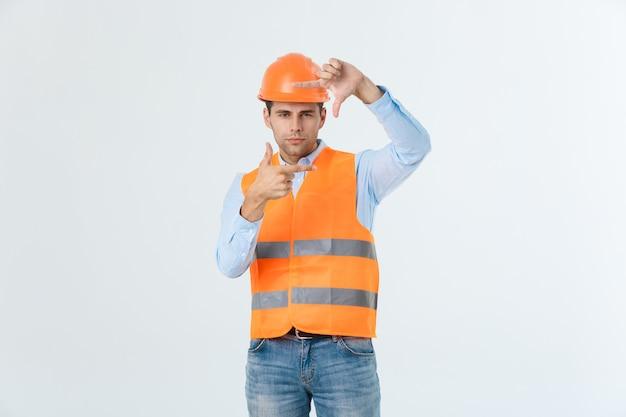 Bel giovane architetto uomo con indossare il casco di sicurezza su sfondo isolato rendendo il telaio con le mani e le dita con la faccia felice. creatività e concetto di fotografia.