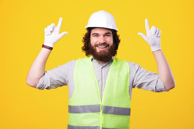 Young handsome architect is smiling at the camera and is pointing with his thumbs up near a yellow wall