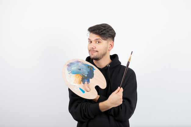 Young handsome artist holding paintbrushes and palette with colors