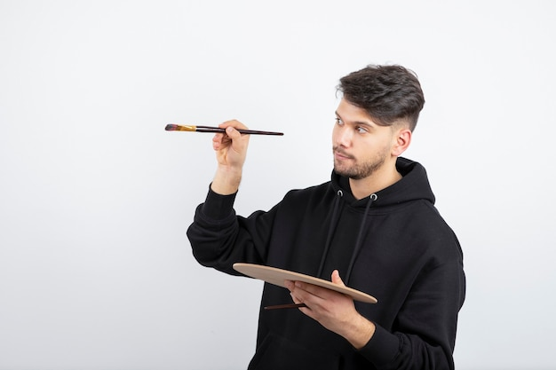 Young handsome artist holding paintbrushes and picking color from palette