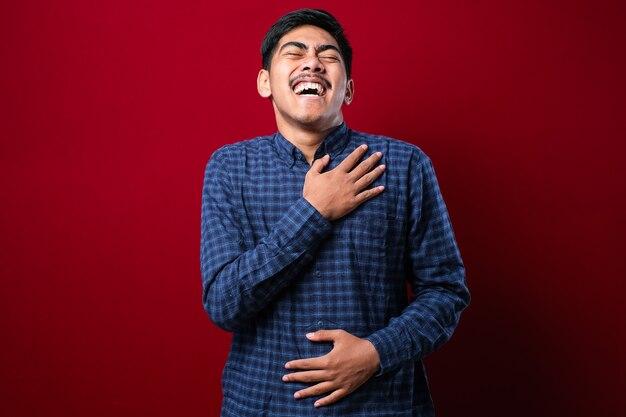 孤立した赤い背景の上に立っているカジュアルなシャツを着ている若いハンサムなアジアの少年は、体に手を添えて面白いクレイジーな冗談を言っているので、笑顔で大声で笑っています。
