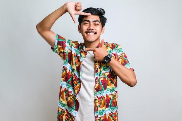Молодой красивый азиатский мальчик в повседневной рубашке, стоящий на изолированном красном фоне, улыбаясь, делает рамку руками и пальцами с счастливым лицом. концепция творчества и фотографии