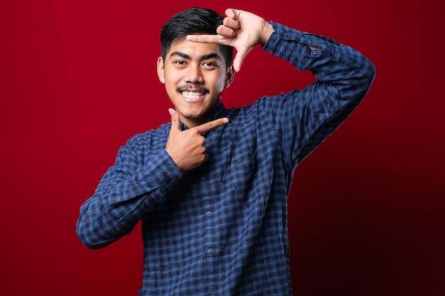 캐주얼 셔츠를 입은 젊고 잘생긴 아시아 소년은 고립된 붉은 배경 위에 서서 행복한 얼굴로 손과 손가락으로 틀을 만들고 웃고 있습니다. 창의력과 사진 개념