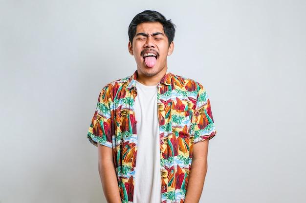 面白い表情で幸せな舌を突き出して白い背景の上に立っているカジュアルなシャツを着ている若いハンサムなアジアの少年。感情の概念。