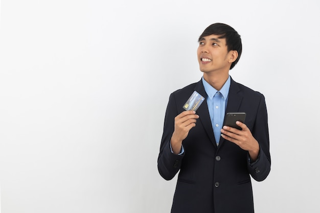 Young handsome asian business man holding a black smartphone,credit card and thinking an idea while looking up