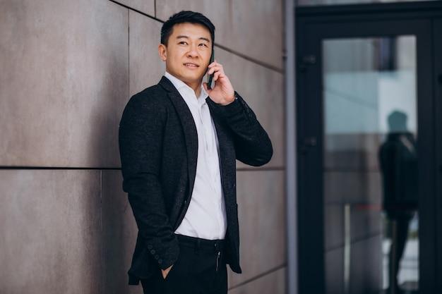 전화를 사용 하여 검은 양복에 젊은 잘 생긴 아시아 비즈니스 남자