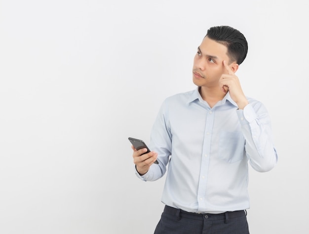 Молодой красивый азиатский бизнесмен играя smartphone и думая изолированный на белизне