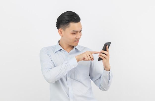 Молодой красивый азиатский бизнесмен играя smartphone с усмехаться изолированный на белизне