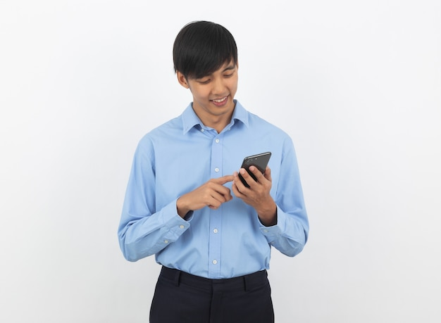 Young handsome asian business man playing smartphone with smiling isolated on white