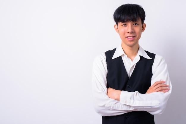 白い壁に対して若いハンサムなアジアのビジネスマン
