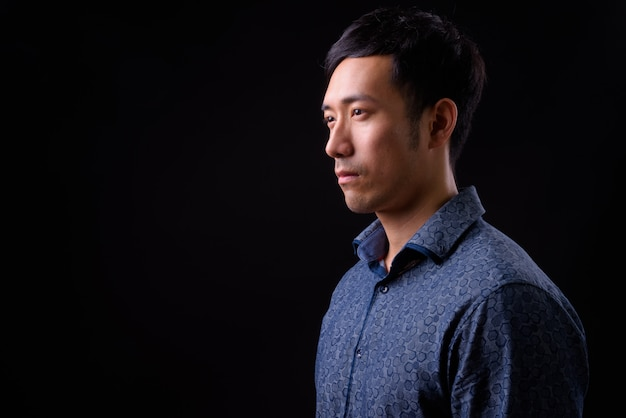 Молодой красивый азиатский бизнесмен на черной стене