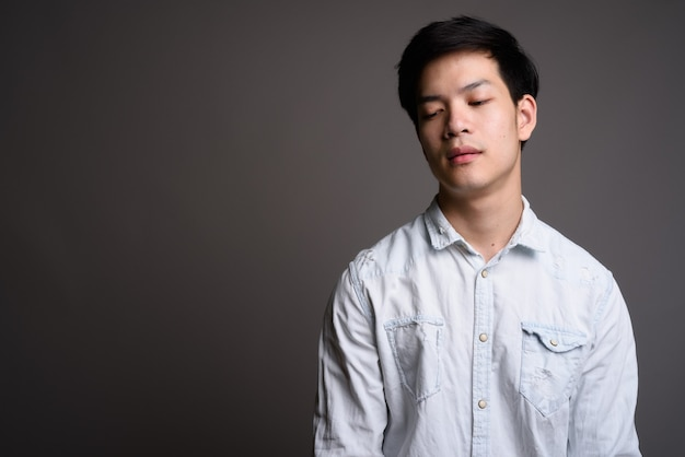Young handsome asian businessman wearing white shirt on gray