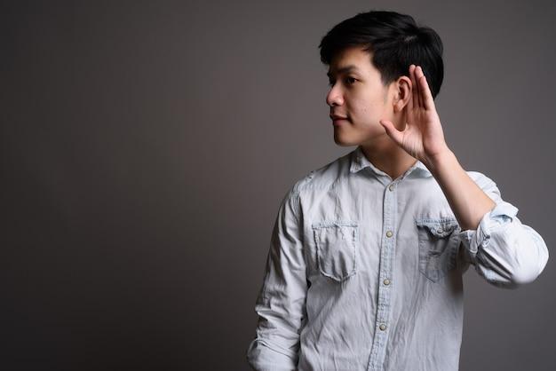 灰色の白いシャツを着ている若いハンサムなアジアの実業家