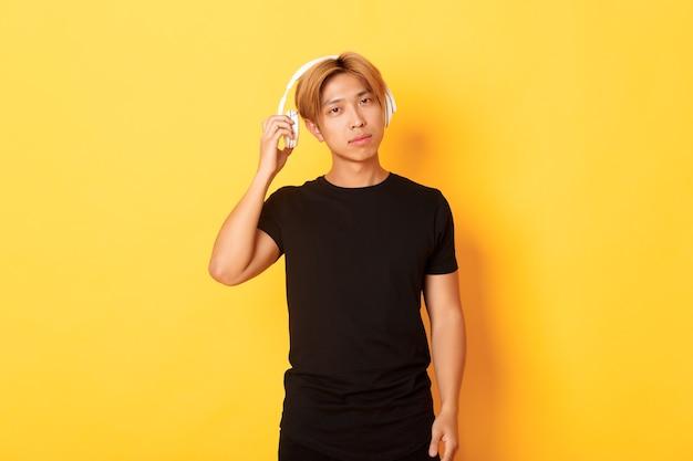 Молодой красивый азиатский парень со светлыми волосами, снимает наушники, чтобы послушать вас, стоя на желтой стене