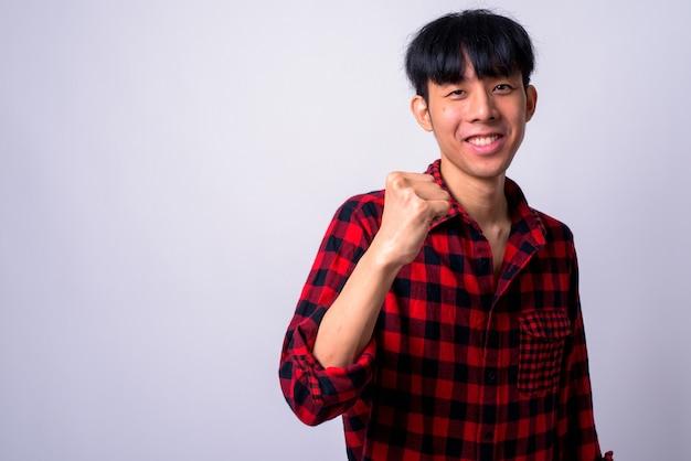 白い壁に対して若いハンサムなアジアの流行に敏感な男
