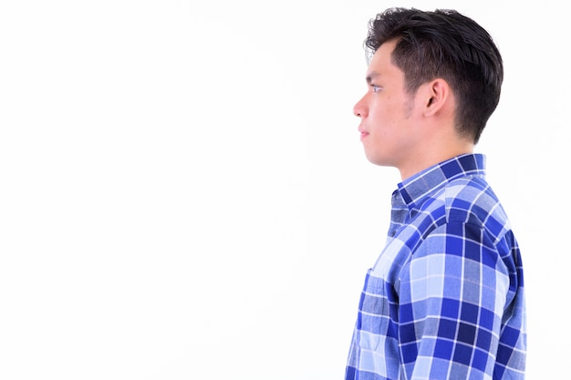 Young handsome asian hipster man isolated against white wall