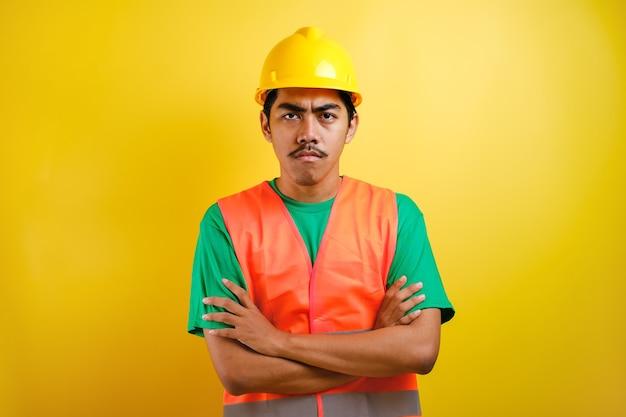 주황색 조끼와 보안 헬멧을 쓴 젊고 잘생긴 아시아 인도 노동자 남성은 회의적이고 긴장하며 팔짱을 끼고 얼굴에 비승인 표정을 짓고 있습니다. 부정적인 사람.