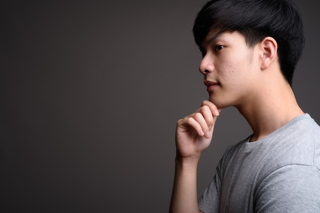 Young handsome asian man on gray