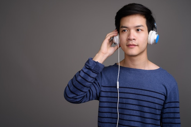 Young handsome asian man listening to music on gray
