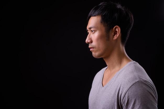 Молодой красивый азиатский мужчина на черной стене
