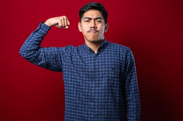 腕の筋肉が誇らしげに笑っているカジュアルな服を着て赤い背景の上の若いハンサムなアジア人。フィットネスのコンセプト。